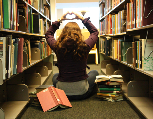 Student sitting in library making a heart shape with her hands