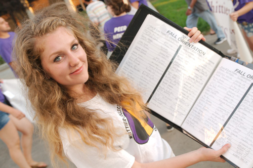 New Student holding President's Matriculation book